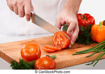Cutting tomatoes - Image of male hand with knife cutting...