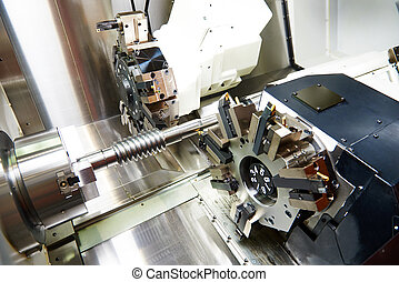 metalworking industry: cutting tool processing steel metal shaft on lathe machine in workshop