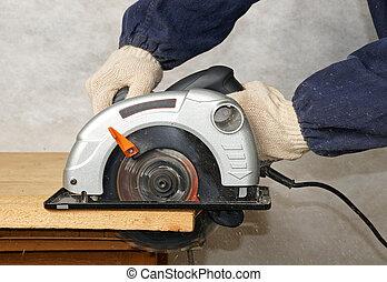 Cutting tool - Man cuts wood with electric circular saw