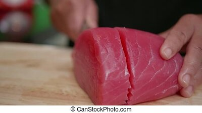 Cutting up raw fillet of salmon on a wooden cutting board...