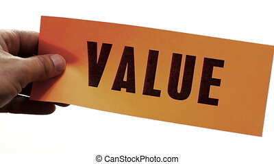 Cutting a bright orange piece of paper with the word value printed on it as a cutting into value concept.
