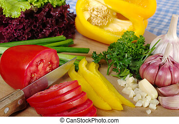 Cutting various vegetables for a salad on wooden board