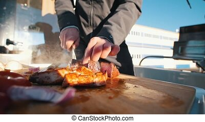 Cutting with knife steaks on the boat. Medium rare....