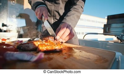 Cutting with knife steaks on the boat. Telephoto shot