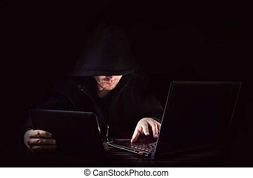 Cyber attack with unrecognizable hooded hacker