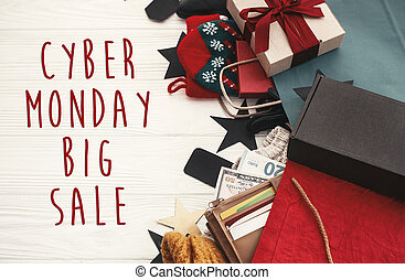 Cyber Monday big sale text sign. Special discount christmas offer. Christmas shopping. Gift boxes, credit cards and money in wallet, bags, clothes, tags on rustic wood