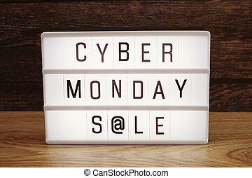 Cyber Monday Sale word in light box on wooden background