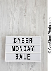 'Cyber monday sale' words on a lightbox on a white wooden background, top view. Overhead, from above, flat lay. Copy space.