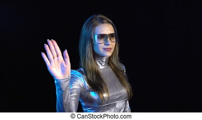 Cyber young woman in silver clothing turning over the virtual pages