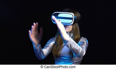 Cyber young woman in silver clothing wearing virtual reality googles
