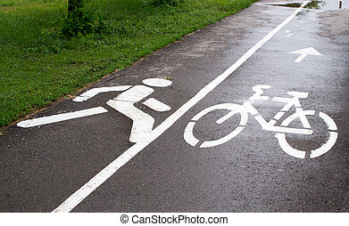 Cycle sign and pedestrian walkway in white paint on tarmac