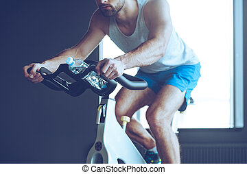 Cycling and energy. Part of young man in sportswear cycling at gym