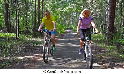 Cycling couple - Couple having fun cycling in the park ...