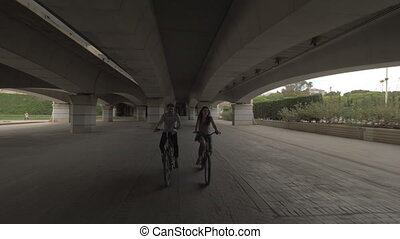 Cycling forward together - A young couple on bicycles riding...