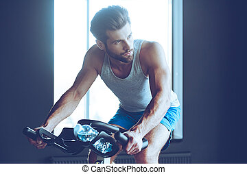 Cycling hard. Young handsome man in sportswear looking away while cycling at gym
