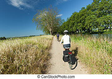 Cycling in nature - Woman and man cycling on path near river...