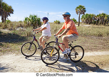 Cycling in Shades - Senior couple riding bikes at the beach,...