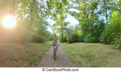 Cycling in the park. Girl riding a bike on a forest trail