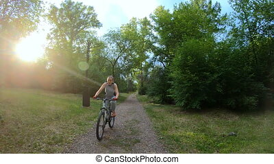 Cycling in the park. Girl riding a bike on a forest trail. Slow motion