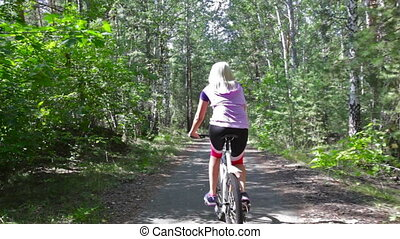 Cycling lady - Rear view of a woman cycling through the...