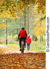cycling outdoors man on bike, golden autumn in park