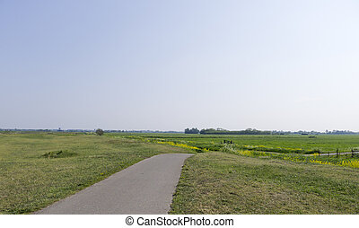 Narrow cycling path through a rural / agrarian landscape in Holland.