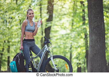 Cycling woman is refreshing with drink