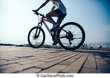 Cycling woman riding mountain mike on sunrise seaside