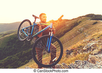 cycling. young man with bicycle on nature in mountains