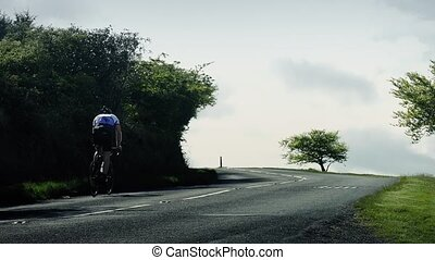 Cyclist And Car On Hillside - Man cycles on road in the...