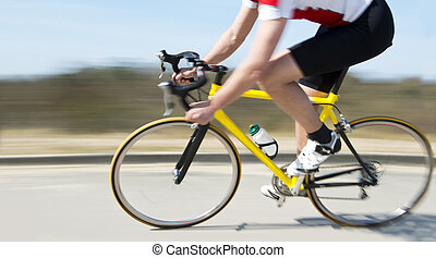 Cyclist at speed - Cyclist on a racing bike speeding past on...