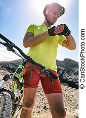 Cyclist biking looking at smartwatch while riding road bike. Athlete biker using activity tracker gps fitness watch on biking workout in sunset. Sports man using his watch app for fitness tracking