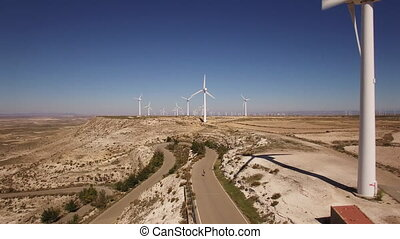 Cyclist climbing to windmill array - Aerial view of cyclist...