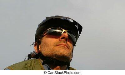 cyclist closeup against blue sky on a sunny day