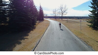 Cyclist cycling through a country road in forest 4k - Rear...