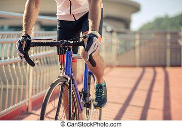 Cyclist feet pedaling a bicycle on bridge