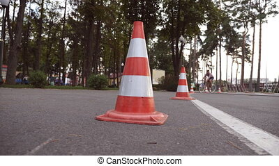 Cyclist go round traffic cones. Young handsome man riding a...