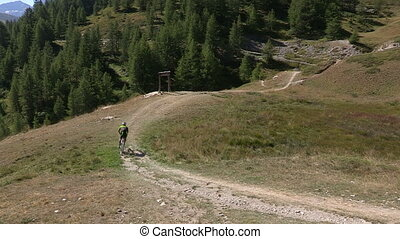 Cyclist going downhill on trail