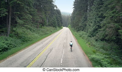 Cyclist Going Up Highway Through The Forest - Aerial view...