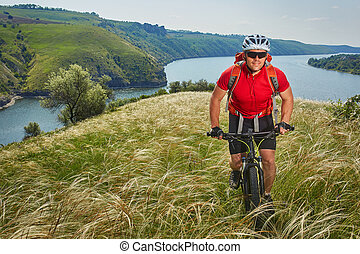 Cyclist has adventure on his mountain bike through green meadow against beautiful sky.