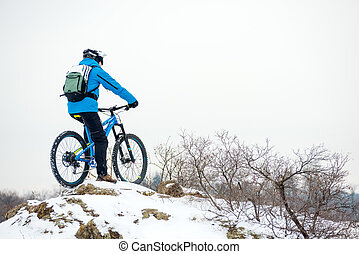 Cyclist in Blue Resting with Mountain Bike on Rocky Winter Hill. Extreme Sport and Enduro Biking Concept.