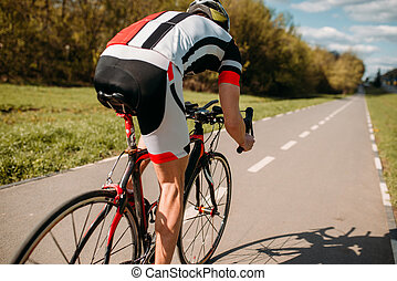 Cyclist in helmet and sportswear rides on bicycle