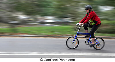 Cyclist in motion blur with blurred urban background