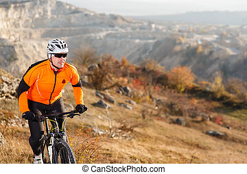 Cyclist in Orange Jacket Riding the Bike on the Rocky Trail. Extreme Sport Concept. Space for Text.