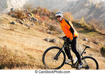 Cyclist in Orange Jacket Riding the Bike Rocky Hill. Extreme Sport Concept. Space for Text.