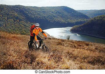 Cyclist in orange jacketr stands with his bike under river against beautiful landscape with mountain.