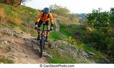 Cyclist in Orange Riding the Mountain Bike on the Autumn Rocky Trail. Extreme Sport and Enduro Biking Concept.