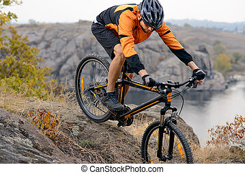 Cyclist in Orange Wear Riding the Bike Down Rocky Hill under River