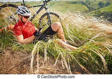 Cyclist in Red Jacket and Helmet Resting near Mountain Bike on the Rocky Hill. Adventure and Travel Concept.