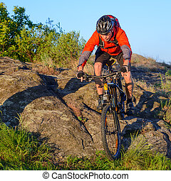 Cyclist in Red Jacket and Helmet Riding Mountain Bike Down Rocky Hill. Adventure and Extreme Sport Concept.